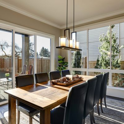 Sun filled dining room in new luxury home boasts Rustic wood dining table with leather chairs surrounded by sliding glass doors which lead out to the patio. Northwest USA